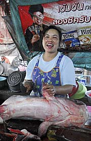 Market Woman chopping a big Catfish by Asienreisender